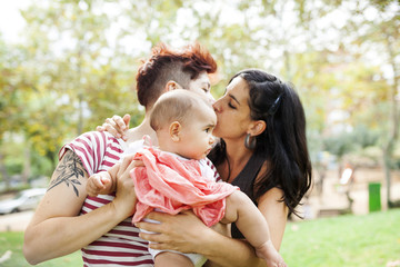 Kissing lesbian couple with baby girl