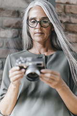 Woman with long grey hair holding camera