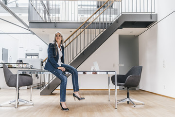Businesswoman with long grey hair sitting on desk in office