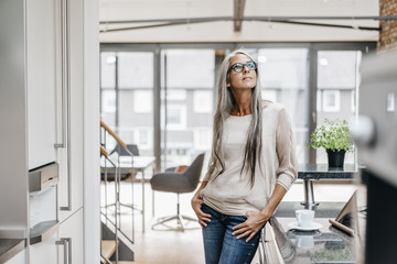 Woman with long grey hair standing in office