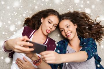 happy teenage girls on floor and taking selfie