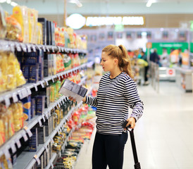 Woman shopping in supermarket reading product information. Checking list.