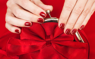 Beautiful small red female purse in hands of young woman and red evening dress. Accessory and clothes perfectly matching to each other. Fingernails with beautiful professional red manicure.