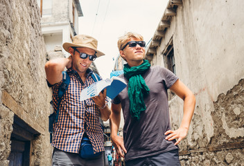 Two tourists try to navigate with guidebook on unknown asian str