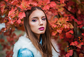 beautiful and fashionable girl in the autumn viburnum
