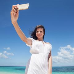 Woman taking selfie on beach