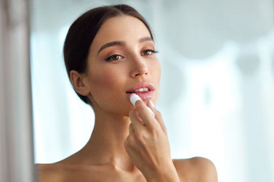 Beautiful Woman With Beauty Face Applies Balm On Lips. Skin Care