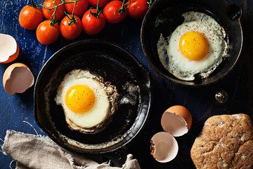 Aluminium Prints Egg Fried eggs in skillets on wooden background