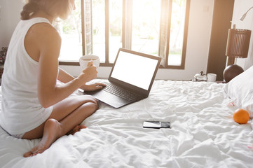 Young lady freelancer sitting on the bed in hotel room in front of window and working in laptop. Wide angle.