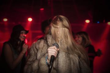 Young woman singing karaoke