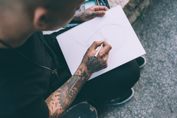 Close up on the hands of young hispanic man tattoed sketching on sketchbook - artist, drawning, creative concept