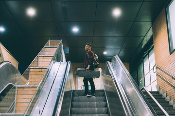 Young hispanic man tattoed on a escalator holding a skater, wearing backpack - sportive, rebel concept