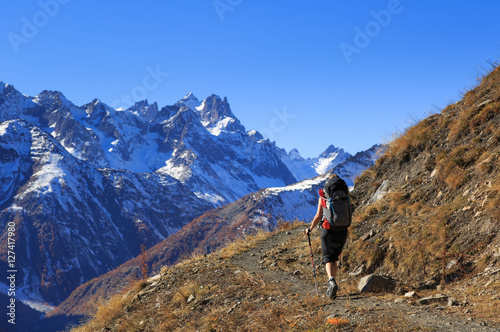 Fotomurales Female hiker on a trail in the French Ercins mountains on an autumn day.
