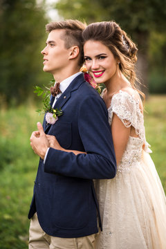 Bride and groom embracing in the park, look at camera, portrait