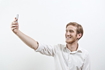 Young Adult Man in White Shirt Takes a Selfie with His Mobile Phone