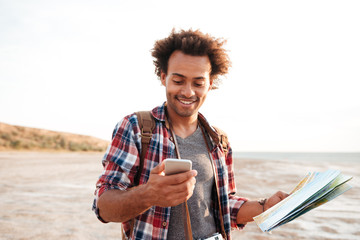 Smiling african man using map and cell phone outdoors