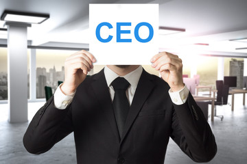 businessman hiding face behind sign ceo