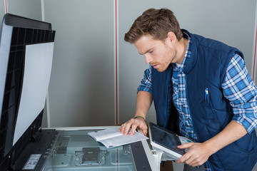 Man reading instructions to repair photocopier