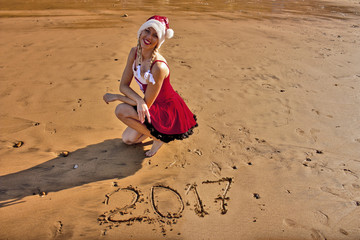 Woman in red dress and Christmas hat on the beach with drawing on the sand digits 2017