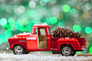 Christmas Toy Truck Close Up With Pine Cone On Wooden Table With Snow.