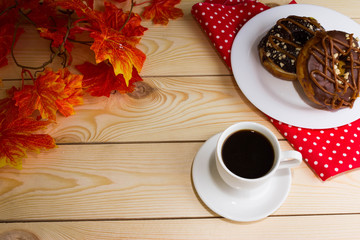 A cup of coffee with a chocolate donuts and autumn leaves