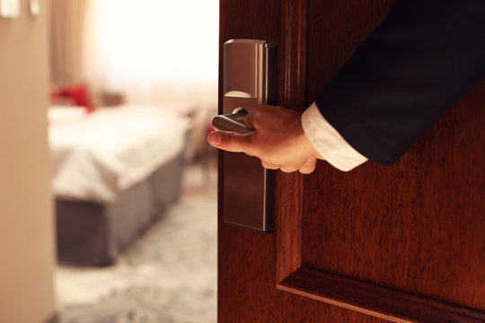 Hand of businessman opening hotel room