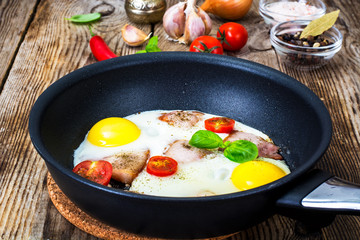 Foto op Canvas Gebakken Eieren Fried eggs with bacon and tomatoes in a pan