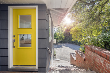 Modern yellow front door with stainless steel handle and glass.