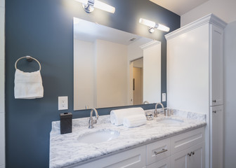 Blue and white bathroom with oval marble double sink.