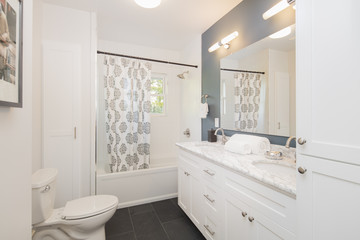 Bathroom with double oval marble sink and shower curtain.