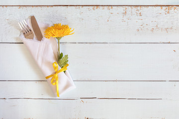 Yellow chrysanthemum flowers, napkin, fork and knife tied with a yellow ribbon on light wooden background.