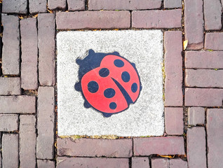 Manhole cover on pavement with patterns, Amsterdam