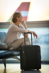 Young female passenger at the airport, waiting for her flight