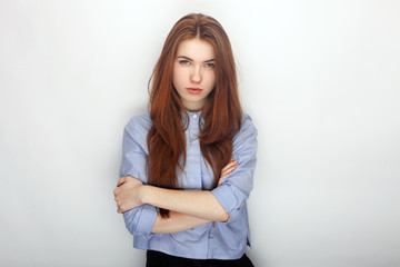 Young serious angry redhead beautiful woman in shirt portrait on a white background hugging herself
