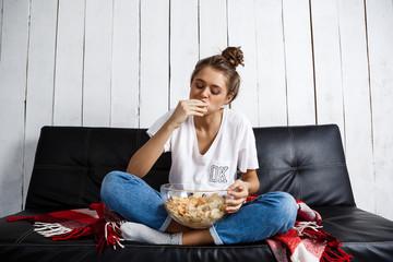 Beautiful domestic girl eating chips, watching tv, sitting at sofa.