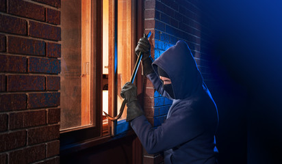 Burglar Using Crowbar To Break Into a House at night with room left and right for type