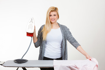Happy woman ironing creased clothes