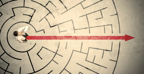 Wall Mural - Business person standing in the middle of a circular maze