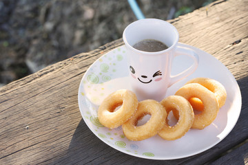 A cup of coffee and donuts on wooden table in the morning