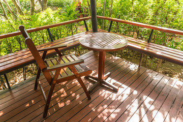 Wooden table and chairs in the Green trees garden.