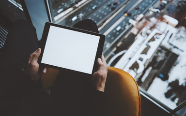 Close up view of mock up template of tablet pc in hands of man sitting near window of skyscraper, using digital tablet with blank screen for your text message, winter cityscape and highway outside