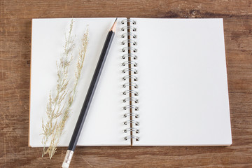 Pencil and notebook on wooden table background