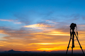 A camera set on a tripod aimed at a silhouette of a landscape at sunset