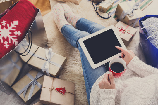Woman makes christmas shopping online with tablet, above view