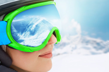 WinterSport, Snowboarding - portrait of young snowboarder girl at the ski resort.A Mountain Range Reflected in the Ski Mask