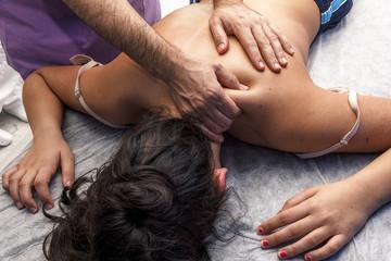 Fisioterapeuta trabajando. Quiromasajista terapéutico trabajando. Tratamiento de sobrecarga muscular.