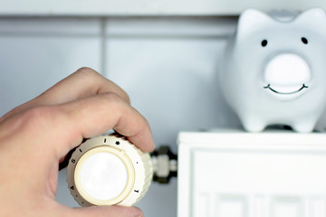 Close-up Of a Mans Hand Adjusting Thermostat With Piggy Bank On Radiator