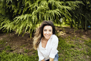 Beautiful, young, European woman smiles at camera in nature