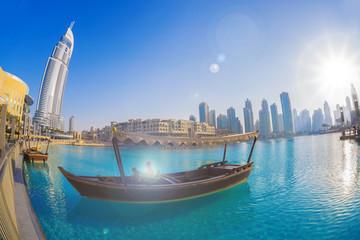Dubai lagoon with boat against sunset in UAE