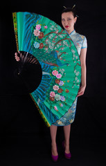 elegant, beautiful girl with a big Chinese fan, a woman in a green dress